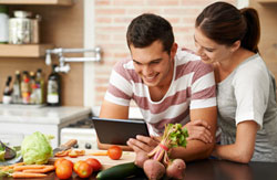 Couple holding tablet in kitchen